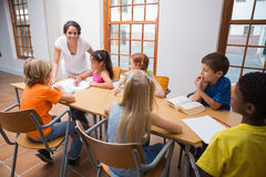 Pretty teacher standing with pupils at desk Royalty Free Stock Images