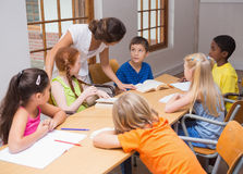 Pretty teacher standing with pupils at desk Stock Image