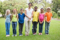 Pretty teacher standing with pupils outside Stock Images