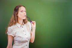 Pretty teacher or student holding glasses at classroom, university Stock Photo