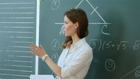 Pretty teacher talking to the pupils in classroom. Professional shot on Lumix GH4 in with high 4K resolution. You can use it e.g in your school, education Royalty Free Stock Images