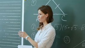 Pretty teacher talking to the pupils in classroom. stock footage