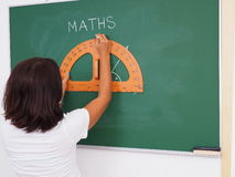 Pretty teacher uses a protractor stock photos