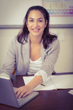 Pretty teacher working with laptop in a classroom Stock Image
