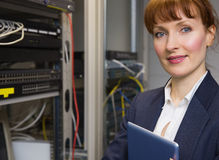 Pretty technician smiling at camera beside open server holding tablet pc Royalty Free Stock Photo