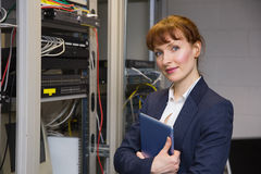 Pretty technician smiling at camera beside open server holding tablet pc Royalty Free Stock Photos