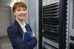 Pretty technician smiling at camera beside server holding tablet pc Stock Images