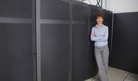 Pretty technician smiling at camera beside server towers Royalty Free Stock Image