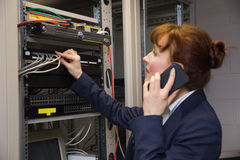 Pretty technician talking on phone while fixing server Royalty Free Stock Photo