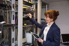 Pretty technician using tablet pc while fixing server Royalty Free Stock Images