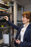 Pretty technician using tablet pc while fixing server Royalty Free Stock Photography