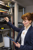 Pretty technician using tablet pc while fixing server Stock Photography