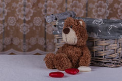Pretty teddy bear is sitting with candy and waiting his beloved. Royalty Free Stock Photo
