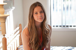 Pretty Teen in Bedroom. A portrait of a beautiful teenage girl in a bedroom brightly lit by natural light Royalty Free Stock Photography