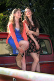 Pretty Teen BFF Girls. Two happy pretty teenaged girls with long brown hair, hanging out laughing together in the back of a pickup. Shallow depth of field Stock Photography