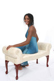 Pretty Teen in Blue Gown Sitting on Bench. Attractive African American teen wearing a blue sparkly gown, sitting on an ivory bench against a white backdrop Stock Photography
