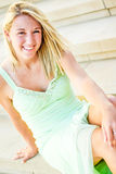 Pretty teen girl with blonde hair. Pretty beautiful young teenage girl / woman / female with blonde hair. wearing elegant mint green formal prom dress. sitting Royalty Free Stock Photo