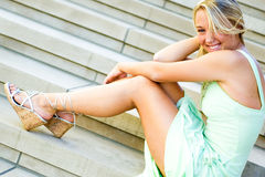 Pretty teen girl with blonde hair. Pretty beautiful young teenage girl / woman / female with blonde hair. wearing elegant mint green formal prom dress. sitting Royalty Free Stock Image