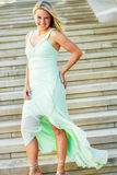 Pretty teen girl with blonde hair. Pretty beautiful young teenage girl / woman / female with blonde hair. wearing elegant mint green formal prom dress. standing Royalty Free Stock Photo