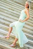 Pretty teen girl with blonde hair. Pretty beautiful young teenage girl / woman / female with blonde hair. wearing elegant mint green formal prom dress. standing Stock Image