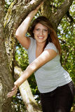 Pretty teen girl climbing a tree Stock Photo