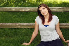 Pretty teen girl in grass by fence Royalty Free Stock Photography
