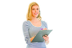 Pretty teen girl in headset writing in clipboard Stock Images