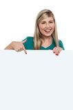 Pretty teen girl indicating downwards over ad board. Cheerful teenager girl indicating downwards over blank white ad board Stock Photos