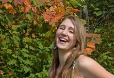Pretty Teen Girl Laughing. Pretty teen girl is happy and laughing against a backdrop of fall autumn foliage.  She's natural looking with minimal makeup and a Royalty Free Stock Image