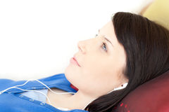 Pretty teen girl listening music lying on a sofa Royalty Free Stock Photos
