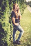 Pretty teen girl in with hairs. Pretty Teen girl posing outdoors in nature, long brown hairs, wearing jeans stock photo