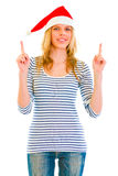 Pretty teen girl in Santa hat pointing up Royalty Free Stock Photo