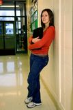 Pretty Teen Girl in School. Teen girl with books waits in school corridor Royalty Free Stock Image