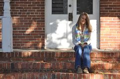 Pretty Teen Girl Sits on Front Steps Royalty Free Stock Photos
