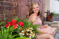 Pretty Teen Girl Sitting on Step. Beautiful and cute teenage girl smiling / laughing / giggling with shoulder length blonde hair wearing white shorts and a Royalty Free Stock Photo