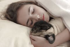 Pretty teen girl sleeps hugging a pug dog in bed royalty free stock images