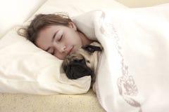 Pretty teen girl sleeps hugging a pug dog in bed stock photos