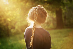 Pretty teen girl standing and thining about something in park. From the back Stock Photos