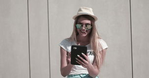 Pretty Teen Girl in Trendy Fashion outfit. Beautiful young woman with hat and sunglasses using tablet in the city stock video