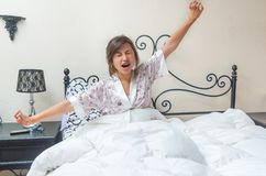 Pretty teen girl waking up in bed Royalty Free Stock Photo