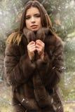 Pretty teen girl is wearing fur coat Stock Photography