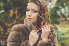 Pretty teen girl is wearing fur coat Stock Photos
