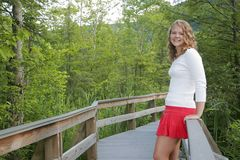 Pretty teen model outdoors. One young blonde teen model posing on a bridge path outdoors half length portrait Stock Photos
