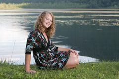 Pretty teen model outdoors. One young blonde teen model posing outdoors for a seated portrait Stock Image