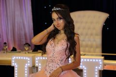 Pretty teen quinceanera birthday girl celebrating in princess dress pink party, special celebration of girl becoming woman. Love and family celebration an Stock Photography
