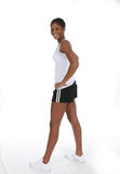 Pretty Teen in shorts and a tank top. Pretty African American teenage girl in shorts and a tank top, standing and looking sideways at the camera Royalty Free Stock Photo