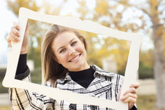 Pretty Teen Smiling in a Park with Picture Frame Stock Photography