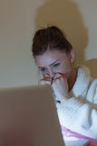 Pretty teen wearing dressing gown watching her laptop in the dar Royalty Free Stock Photos
