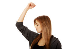 Pretty teen woman sniffing her armpit.  Stock Photo
