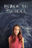 Pretty teenage girl against blackboard with back to school chalk Stock Photography